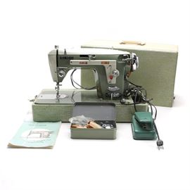 """New Home Electric Sewing Machine Circa 1955: A Mid-Century New Home Double Duty sewing machine. Featured is a vintage sewing machine circa 1955 by The New Home Sewing Machine Company in Los Angeles, California. The machine was manufactured in Japan by Janome and the model number is """"532"""". Included is an instruction manual and a tin with sewing notions."""