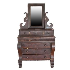 Antique American Empire Style Gentleman's Chest With Mirror: An antique American Empire style gentleman's chest with mirror. This selection includes a rectangular mirror with beveled frame flanked at the bottom by two scrolling side brackets, resting atop a step back three drawer element with locking center drawer. Below the drawered element is a top with three drawers with wood knob pulls, metal escutcheons in the centers, flanked on each side by scrolled stiles which protrude out from the piece and end in bracket feet. This multipart mahogany chest includes flame mahogany veneers and hand dovetail joinery.