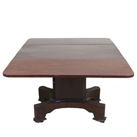 Vintage Drop Leaf Table: A vintage walnut drop leaf table. This rectangular table features a top with two side drop leaves over a rectangular pediment base which rests on bracket legs ending in molding and resting on casters. The table has mortise and tenon construction and includes peg joints and chamfered ends to the base column and the leg sides.