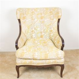 Vintage Bergere Chair With Yellow Floral Upholstery: A bergere club chair with yellow floral upholstery. This vintage accent chair has a bowed back with scrolled walnut stile wings leading into closed arms, oversized removable seat with flat seat rail front over scalloped apron, resting on walnut cabriole legs with pad feet. The chair is covered in a yellow on cream foliate upholstery with piping details.