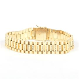 18K Yellow Gold Link and Diamond Bracelet: An 18K yellow gold bracelet accented by small diamonds on the center links.