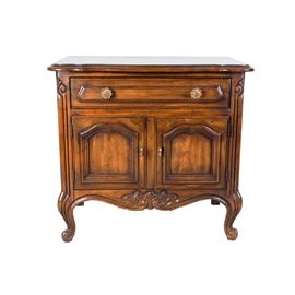 Drexel French Provincial Style Nightstand: A French Provincial style nightstand by Drexel Furniture. This intentionally distressed, walnut stained wooden piece has a beveled top edge with bowed front and curling accents carved to the front stiles and on the cabriole feet. The drawer has two brass-tone floral knobs, and sits above a cabinet with two doors with center framing detail. The curved apron has a fanned scroll carving in the center.