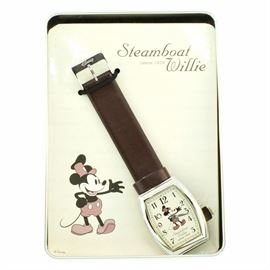 Disney's Steamboat Willie Since 1928 Commemorative Wristwatch: A Disney Steamboat Willie since 1928 commemorative wristwatch. This watch features a rounded rectangular base metal and stainless steel case housing a cream dial. The dial motif depicts the classic Steamboat Willie Mickey Mouse. The case attaches to a brown strap with a buckle closure.