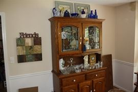Photo of the hutch with the top cabinet closed. There is an accompanying dining room table and chairs.