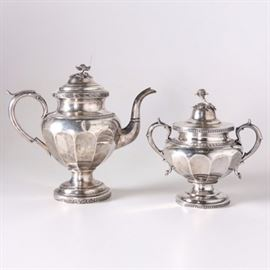 "Antique Coin Silver Lincoln & Foss Teapot and John C Moore Sugar Bowl: An antique coin silver teapot and sugar bowl. The teapot features a fluted urn style body with an ornate flower on the lid and round base, marked ""Lincoln and Foss Boston"" to the underside. The sugar bowl features two handles, a fluted body, a decorative flower on the lid and a round base. The base is marked ""J.C.M New York"" along with a John C. Moore manufacture mark. Both pieces are monogrammed ""Mary Wilson Moore"". The total approximate weight is 59.60 ozt."