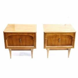 "American of Martinsville Nightstands: A set of American of Martinsville nightstands. Each nightstand features a rectangular top and body with four tapered feet and two drawers set into the front. The top drawer has a handle that runs the full length of the drawer and is made of the same tone of wood as the rest of the stand while the bottom drawer has a brass tone pull handle. The inside of the bottom drawer is marked ""American of Martinsville"".  See matching item 17NAS038-025."