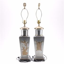 Asian Inspired Silver Tone Urn Table Lamps: A pair of Asian inspired silver tone urn table lamps. Featuring silver tone metallic bodies and tapered wood bases, these single socket table lamps are accented with Asian inspired gold tone motifs. No visible maker's marks.