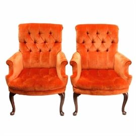 Tufted Velveteen Chairs: A pair of tufted velveteen chairs. These two chairs feature a tufted seat with upholstered tangerine colored velveteen cushions, sock pleated arms, cabriole legs with pad feet and carved scrolled motifs on the knees. These pieces are unmarked.