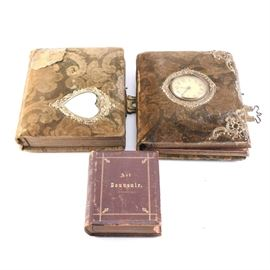 "Victorian Style Photo Booklets: A collection of Victorian-style photo booklets. Featured are two booklets with a fabric cover covering and metallic locket latch. One of the booklets has a clock face to the cover and the other a heart-shaped mirror. Also included is a small booklet with a leather bound cover and title reading ""Art Souvenir"". The booklet contains various printed cards."