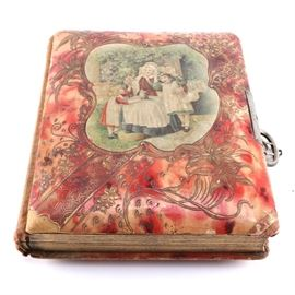 Victorian Photo Album With Albumens and Ambrotypes: A photo from the Victorian era. The piece contains both albumen and ambrotype photos. The album has a red cover with a central reserve depicting a woman with a kitten in her lap who is surrounded by two little girls in pinafores.