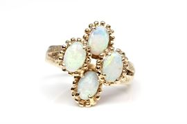 14K Yellow Gold Opal Ring: A yellow gold diamond etched split shank holds four prong set oval cabochon white opal with prong like borders to each.