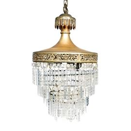 Vintage Chandelier With Crystal Prisms: A vintage chandelier with crystal prisms. This selection features five row of prisms supported by an ornate, brass tone top. It includes four light sockets and bears no visible maker's marks.