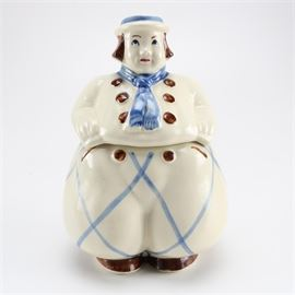 "Circa 1940s Dutch Boy Cookie Jar: A circa 1940s Dutch boy style cookie jar. The jar is in the shape of a portly man with a white and blue ensemble with bobbed brown hair and a blue scarf with six brown buttons and ballooning crisscrossed pants. The jar opens at the waist and is marked ""USA"" to the underside."