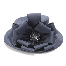 Whittall & Shon Navy Derby Hat: A navy blue Derby hat by Whittall & Shon. This hat is made of navy blue fabric with a large bow to one side. The center of the bow features a clear and navy blue rhinestone pin.