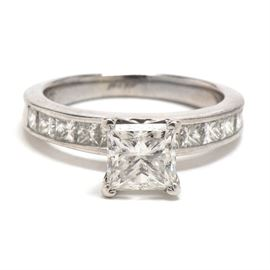 18K White Gold 2.22 CTW Princess Cut Diamond Engagement Ring: An 18K white gold engagement ring featuring princess-cut diamonds. There is a center diamond in a high mounting with additional channel-set diamonds adorning the top half. Total approximate carat weight is 2.22 ctw.