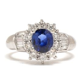 18K White Gold Natural Blue Sapphire Diamond Statement Ring: An 18K white gold statement ring featuring a natural blue sapphire surrounded by a wreath of diamonds with additional diamonds to the shoulders. Total diamond carat weight is 0.57 ctw.