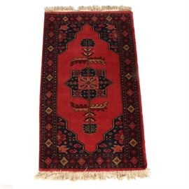 Hand-Knotted Jaipur Caucasian Area Rug: A hand-knotted Jaipur Caucasian area rug. This wool rug features an eight-sided star medallion with floral pendants that reach into a red field. It has corner spandrels with a boteh design and a primary border with repeating lozenges. The rug offers a palette of black, gold, cream, burgundy, and red. It is finished with overcast edges and a natural warp fringe. The rug has a tag to the verso.