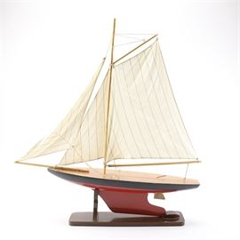 Wooden Model Sailboat: A wooden model sailboat. This large model single-masted sailboat features pinstripe cloth sail and jibs and a solid wood red painted hull. The sailboat mounts on a rectangular brown wood stand with no apparent markings.
