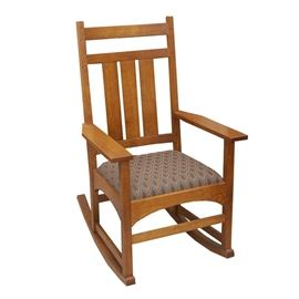 "Stickley Rocking Chair: A Stickley rocking chair. Featured here is a wooden framed rocking chair with a straight mission style design. The padded seat is upholstered in fabric with a diamond pattern containing blues, red, green, and yellow. The underside of this oak rocking chair is branded ""Stickley""."