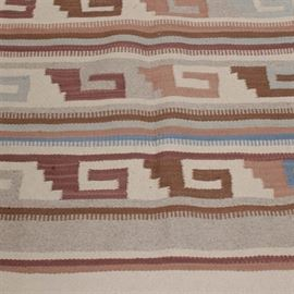 Hand-Woven Southwest-Style Area Rug: A hand-woven southwest-style area rug, in a palette of ivory, tan, terra cotta, brown and blue. The rug is designed with narrow and wide stripes, with geometric patterns in the wide stripes. The short ends of the rug have long, sparse twisted fringe.
