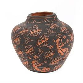 "Navajo Sgraffitto Pot: A Navajo Sgraffito pot. This globular, clay pottery piece has a black overlay with terra cotton colored designs of mountains and people making music. The bottom of the pot is signed ""T. Rail"". Paperwork included with the pottery indicates that it is ""Navajo Etched Pottery""."