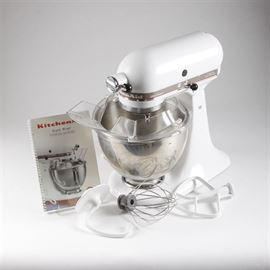 "KitchenAid Mixer with Attachments: A KitchenAid stand mixer. The KitchenAid mixer has a white metal housing, and comes with a four and a half quart stainless steel mixing bowl, a splash guard, a whisk attachment, a dough hook, a paddle attachment and instruction book. The mixer is marked ""Ultra Power"" and is model KSM90PSWH, with serial number WH3280707."