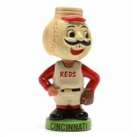 "1962 Reds Bobblehead: A 1962 Cincinnati Reds bobblehead. The bobblehead is Mr. Red with ""REDS"" embossed in red letters on his chest. The base is round green color and the bottom is stamped ""Japan Pat. #218612 S.S. CORP. ©1962"". ""CINCINNATI"" is hand painted on the base. This bobblehead is made of paper mache type of material."