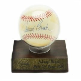 "Johnny Bench Signed Baseball: A Johnny Bench autographed National League (White President) baseball. John signed the ""sweet spot"" with a blue ink pen. The baseball comes in a ball holder that has a wood pressed base. A thin metal plate has the Cincinnati Reds logo engraved as well as ""Johnny Bench Hall of Fame 1989"". His signature has not been authenticated."