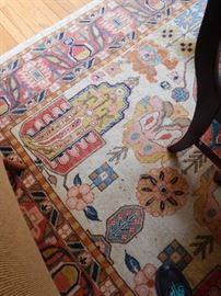 A large and colorful rug in the living room/dining room area.