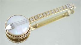 """Lot 8: 14kt gold and mother of pearl banjo pin, set with fifteen round cut diamonds, approx. .75 ctw, 13.3 grams, 2.75""""L"""