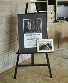 An Ansel Adams exhibition poster that has been signed by Adams, also a copy of the book featuring the photographs of the exhibit.