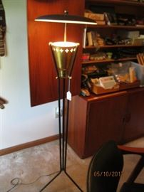 Mid Century floor lamp with disc shade over brass pierced light receptacle supported on three iron rods continuing to feet.