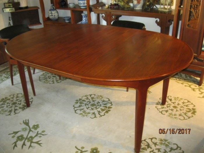 "Danish Modern Round Dining Table with tapered legs. 49"" D, shown with one leaf in. 3 additional leaves, each measuring 19 3/4"" wide. When extended a drop down of two additional legs occurs for added support. In very good used condition."