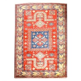 "Hand-Knotted Kazak Fachralo Area Rug: A hand-knotted Kazak Fachralo area rug. This Caucasian rug features a center square with orange motifs on a blue ground. The square is centered on an orange panel with medallion flowers along the sides, with large U-shaped motifs on either end. The orange panel has a dark blue unresolved border with ""S: designs in white and red, with an outer yellow border, also unresolved, with geometric motifs in purple, red and gray. The rug is framed in a zig-zag border of dark blue and red, with short fringe on the ends. There is a label with a number on the underside, otherwise unmarked."