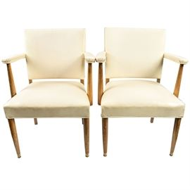 Pair of Mid Century Modern Vinyl Arm Chairs: A pair of midcentury modern vinyl arm chairs. These two chairs feature wooden frames with straight armrest supports and legs. The seats and backs of the chairs are covered in white vinyl upholstery. There is an accentuated white tack design on the back side of the chairs. No maker's marks.