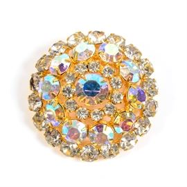 Rhinestone Brooch: A rhinestone brooch. This round brooch features a central rhinestone surrounded by concentric rings of clear and iridescent rhinestones in a gold tone frame with a safety pin clasp. This piece has no apparent marks.