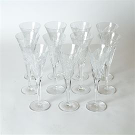 "Collection of Eleven Waterford Crystal Champagne Flutes: A collection of eleven Waterford crystal champagne flutes in a variety of patterns. Each glass is etched on the underside of the base ""Waterford""."