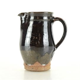 John Tuska Art Pottery Pitcher: A John Tuska (1931 – 1998) original art pottery pitcher. Features a smaller size with glossy brown over glaze and sage tone under glaze. The piece is signed and dated 1994 to the underside.