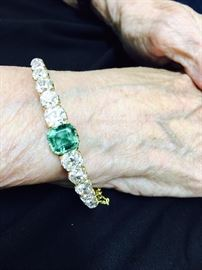 Antique diamond and emerald bracelet.  Set with twelve old mine cut diamonds weighing approx 6 carats total.  Set in the center is a natural emerald of approx 2.25 carats.  Unmarked yellow gold.