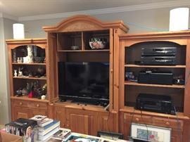 "Entertainment center with central TV unit (holds up to a 40"" TV) and two side bookcases with storage)."