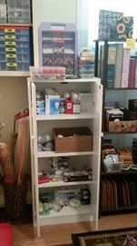 Cabinet full of light bulbs--cabinet SOLD, more beads in containers above, shelving with photo albums