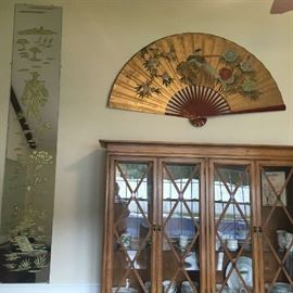 Oriental wall mirrors and decorative fan.