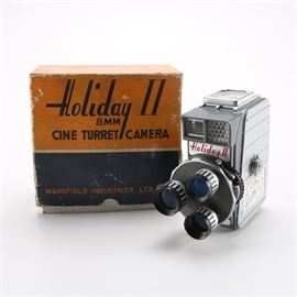 """Mid-Century Mansfield Industries """"Holiday II"""" 8 mm Camera: A mid-century 8 mm camera called the """"Holiday II Cine Turret Camera"""" produced by Mansfield Industries Ltd. in Chicago. This camera has three lenses on a rotating plate including one wide angle lens. It has a cast aluminum body, a gauge along the top to aid in choosing the correct f-stop setting, and a viewfinder in the back. It comes with its original box."""