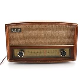 Vintage Zenith Radio: A vintage zenith radio with a brown wood case with a tan front speaker and dual-knob dial panel. This radio features AM and FM radio bands, and has a headphone jack in the back.