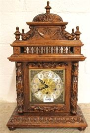 "Highly Carved and Ornate Oak Mantle Clock with Urgos Works  approximately 25 1/2""h x 16""w x 9 1/2""d  Located Inside – Auction Estimate $200-$400"