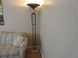 Elegant floor lamp with rod iron and marble base and globe holding up the top metal shade.