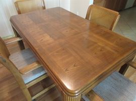 Beautiful solid oak dining / kitchen table with four chairs on wheels. Chairs are also oak with cushioned seats and woven insets on the back. Middle leaf can be removed for a smaller area.