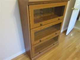 Oak three door book shelf unit; doors have inlaid glass panels for viewing, and two nobs to lift the door and roll it into the unit.