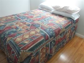 Double size bed; frame on wheels, box spring and mattress with pillows and comforter shown.