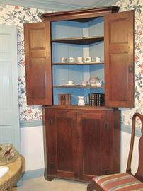 Moravian one piece walnut corner cupboard, circa 1810